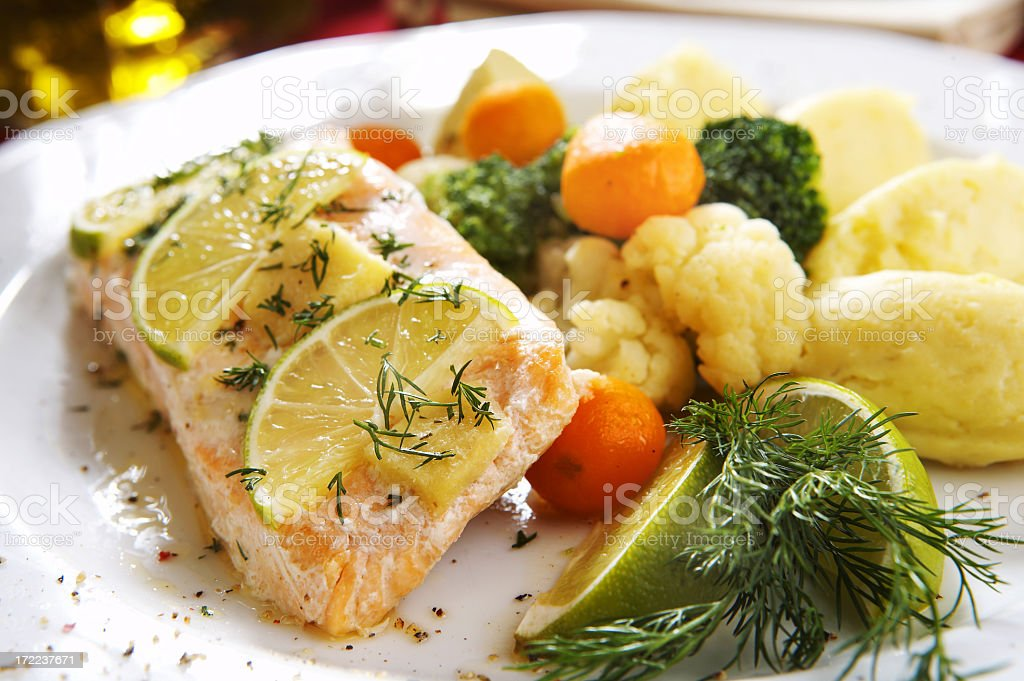 Baked salmon dish with assorted vegetables and lemon stock photo