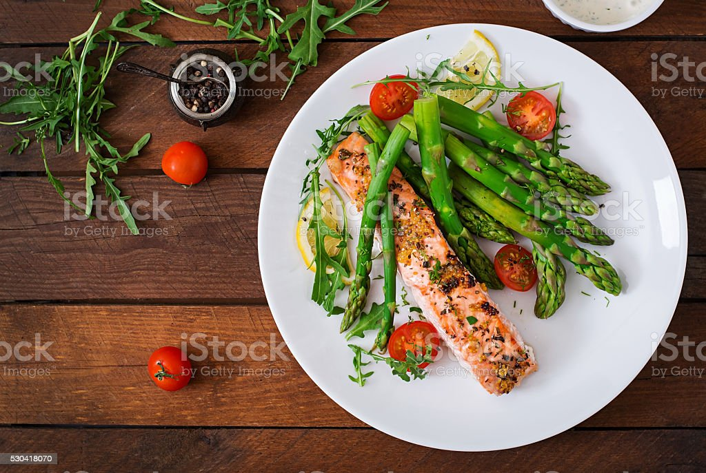 Baked salmon garnished with asparagus and tomatoes with herbs stock photo