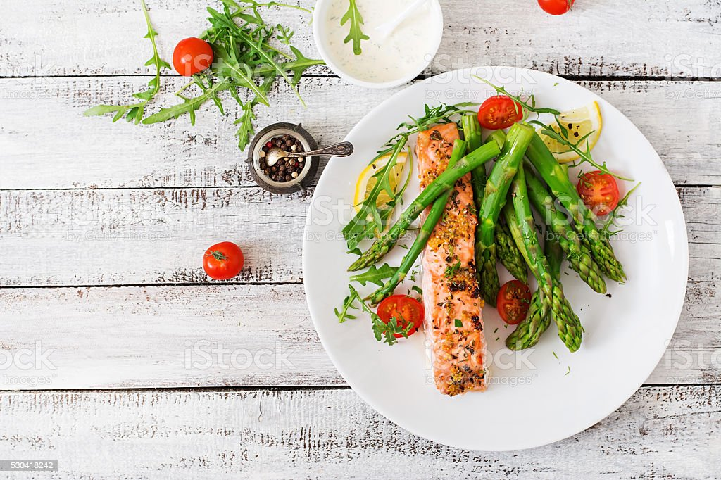 Baked salmon garnished with asparagus and tomatoes with herbs royalty-free stock photo