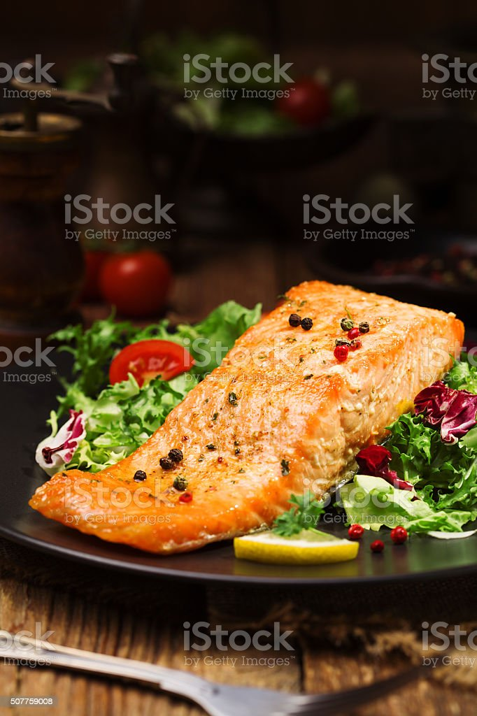 Baked salmon served with fresh vegetables. stock photo