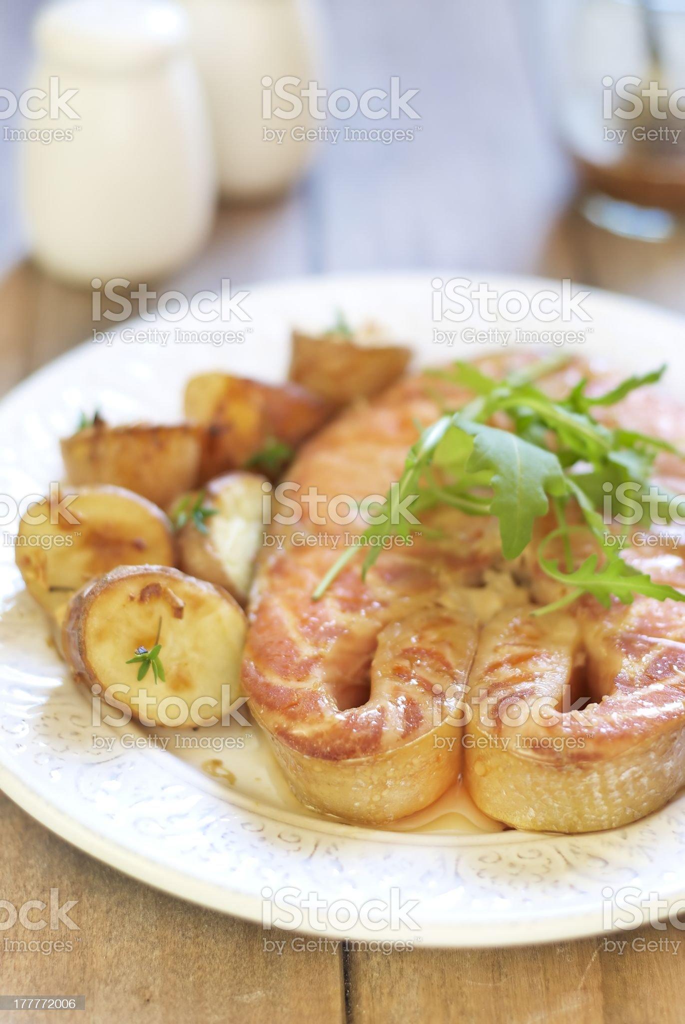 Baked salmon steak with potato and arugula royalty-free stock photo