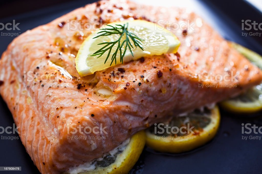 Baked salmon with a slice of lemon and some dill stock photo