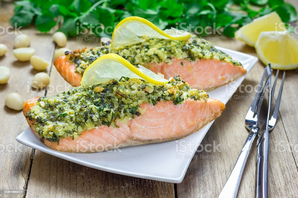 Baked salmon with macadamia-cilantro crust on a white plate stock photo