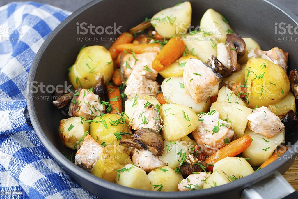 Baked salmon with potato, mushrooms and carrot stock photo