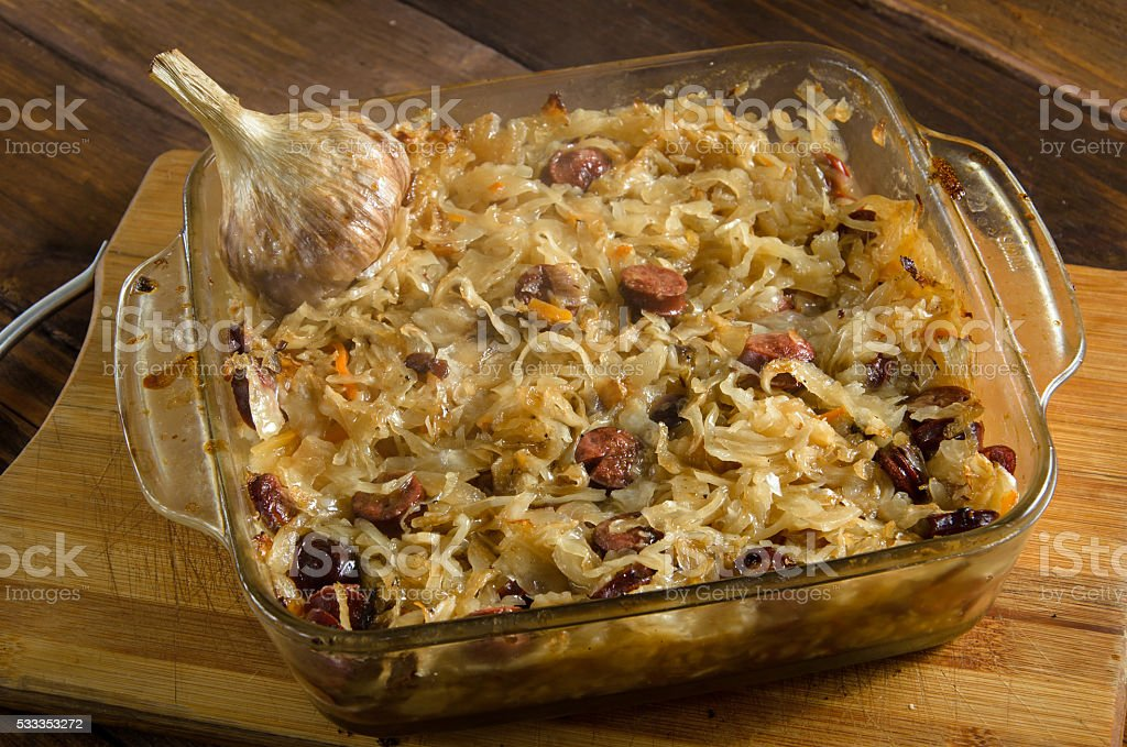 Baked sauerkraut with sausages on wood stock photo
