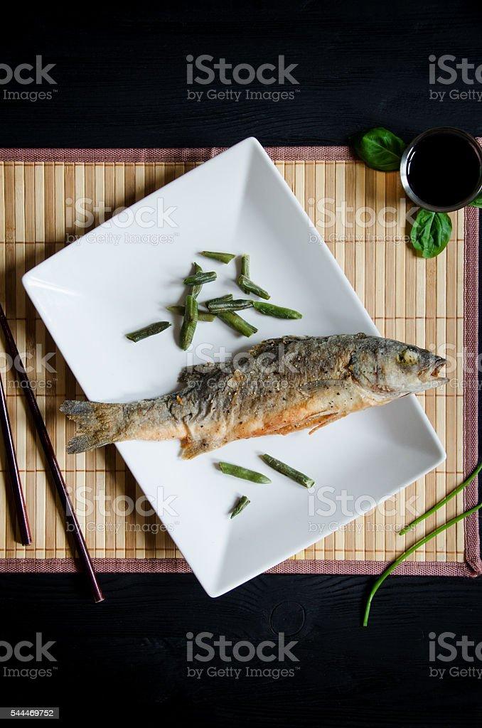 baked sea bass rectangular plate topview stock photo
