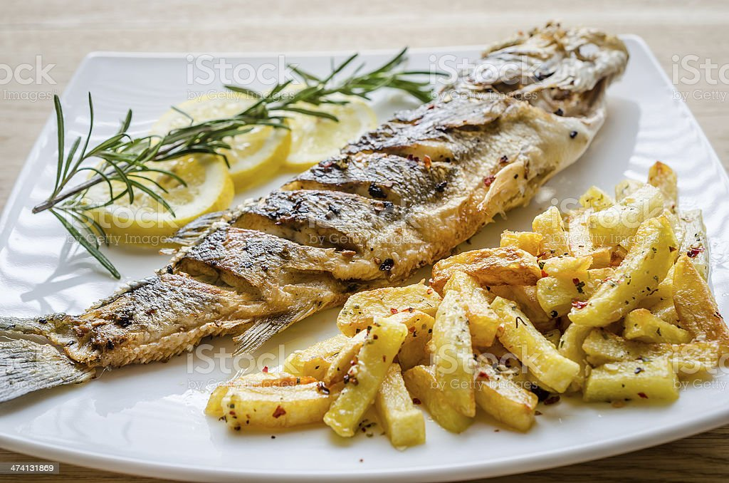 Baked seabass with fried potatoes stock photo
