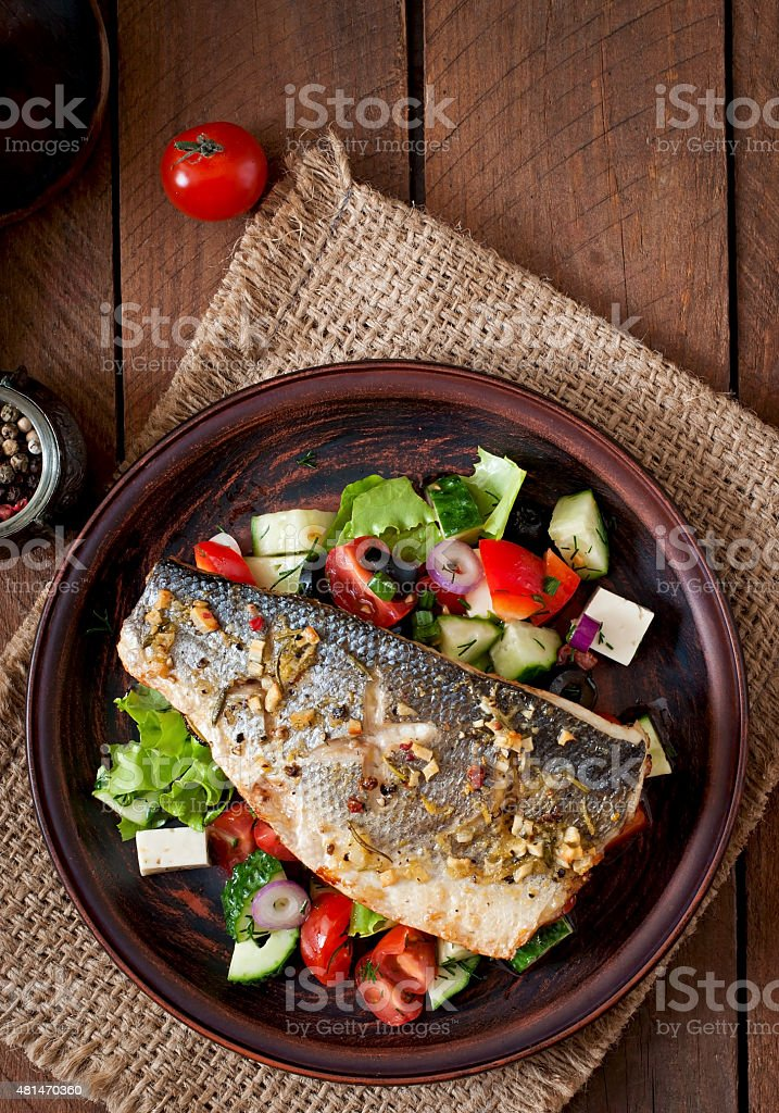 Baked seabass with Greek salad stock photo