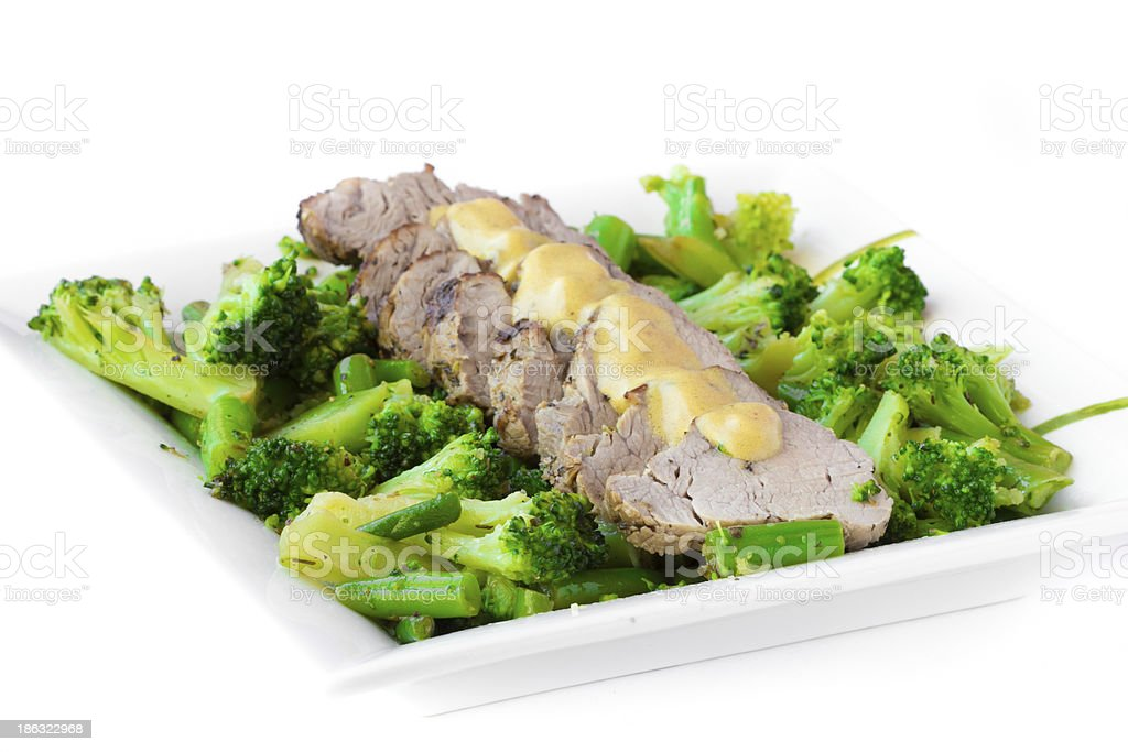 Baked, sliced fillet of pork with green vegetables, broccoli, haricot royalty-free stock photo