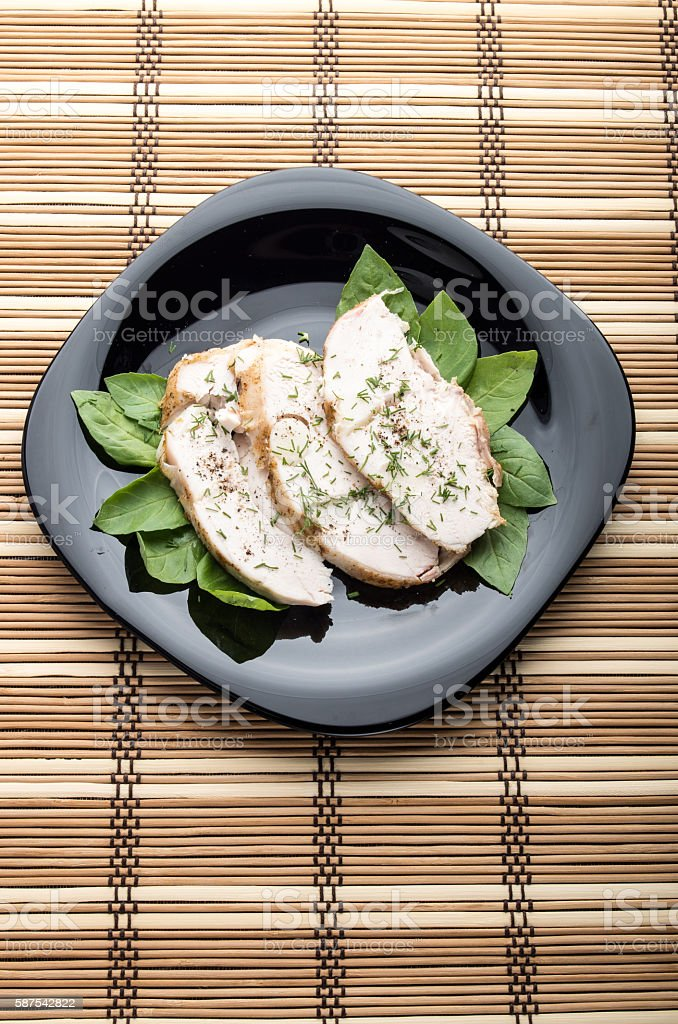 Baked slices of chicken meat on a black plate stock photo