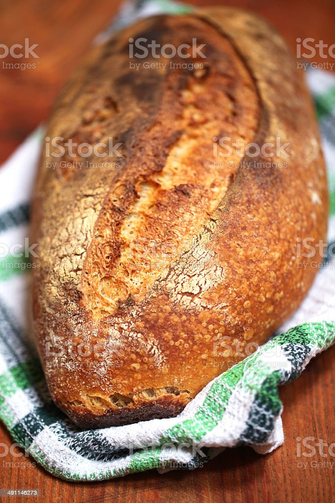 Baked sourdough loaf baked in clay oven, crust and crumb royalty-free stock photo