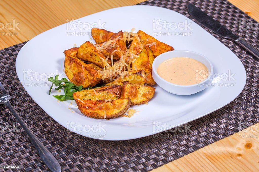 Baked spicy potatoes with cheese served since sauce and herbs stock photo