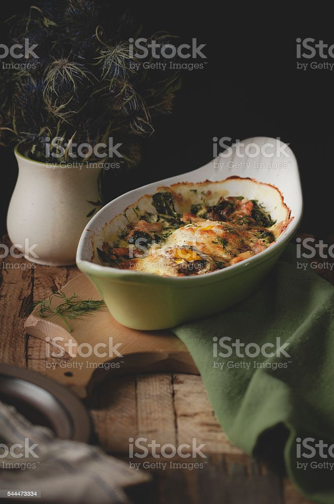 Baked spinach with salmon and eggs stock photo