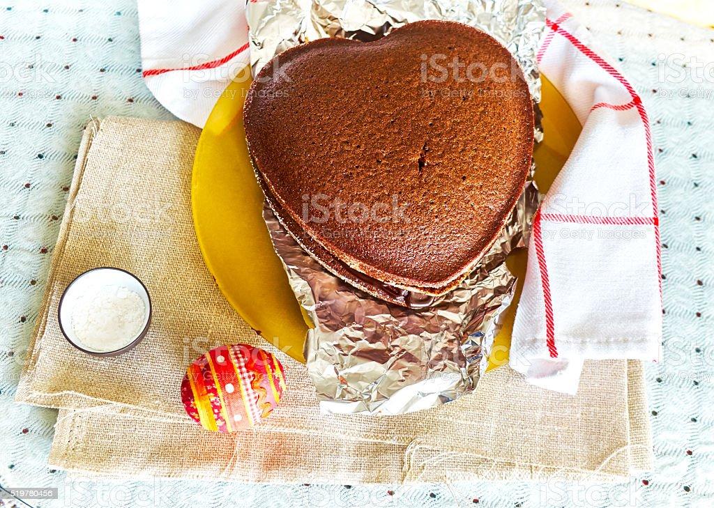 Baked sponge cake in shape heart and souvenir Easter egg stock photo