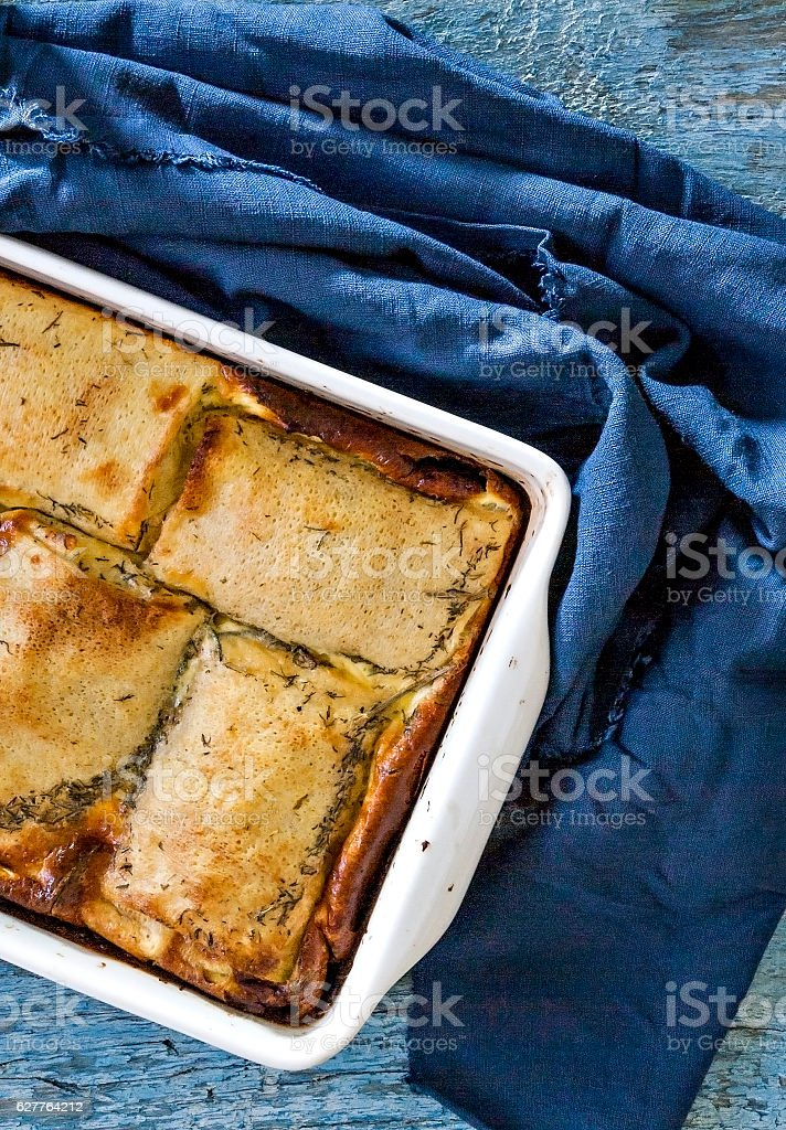 baked stuffed crepes on  blue background and  napkin top view stock photo