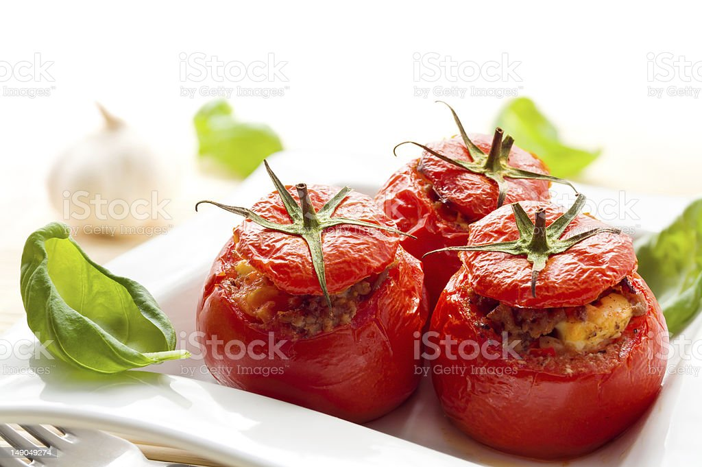 Baked stuffed tomatoes served with fresh basil stock photo