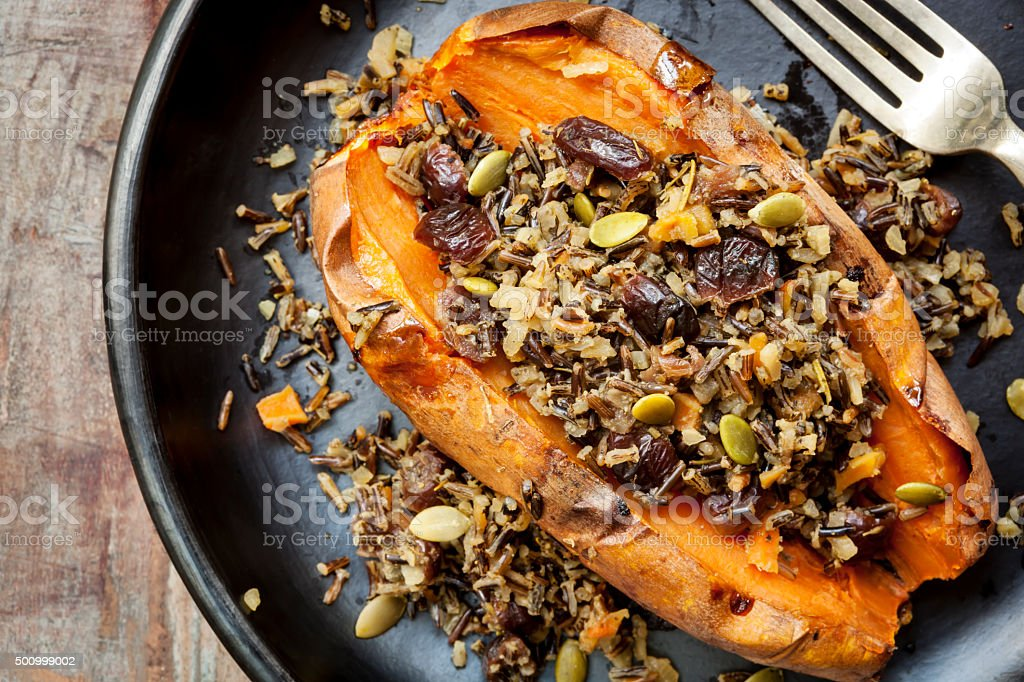 Baked Sweet Potato Stuffed With Wild Rice Seeds and Cranberries stock photo