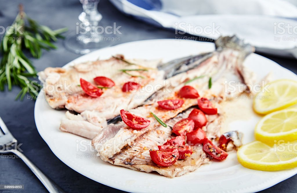 Baked trout with cgerry tomatoes and wine stock photo