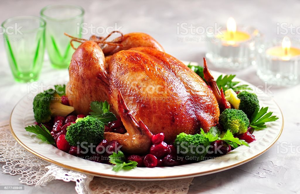 Baked whole chicken with cranberries and broccoli. stock photo