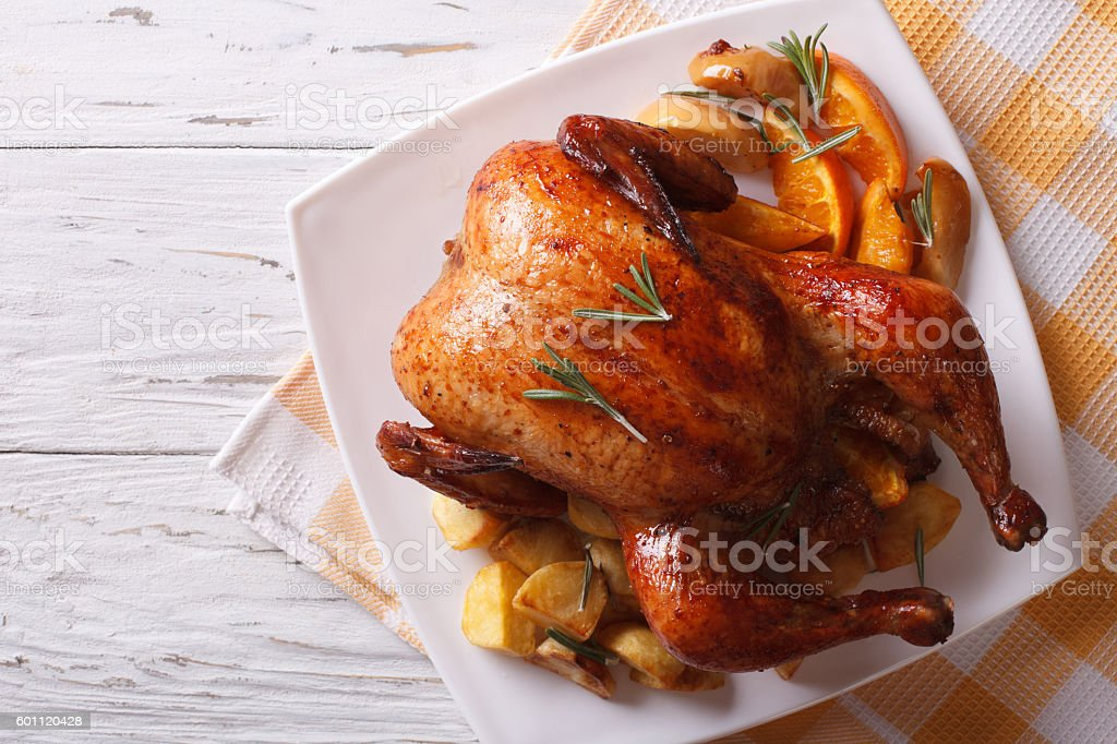 baked whole chicken with oranges on plate. horizontal top view stock photo