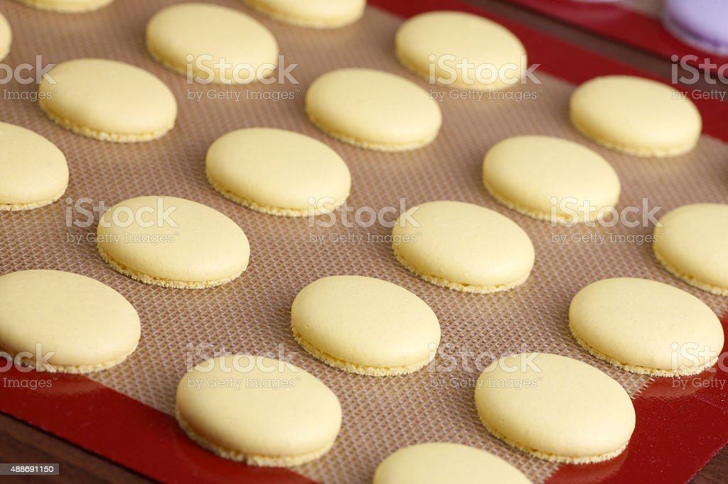 baked yellow macaroon on silicone mat stock photo