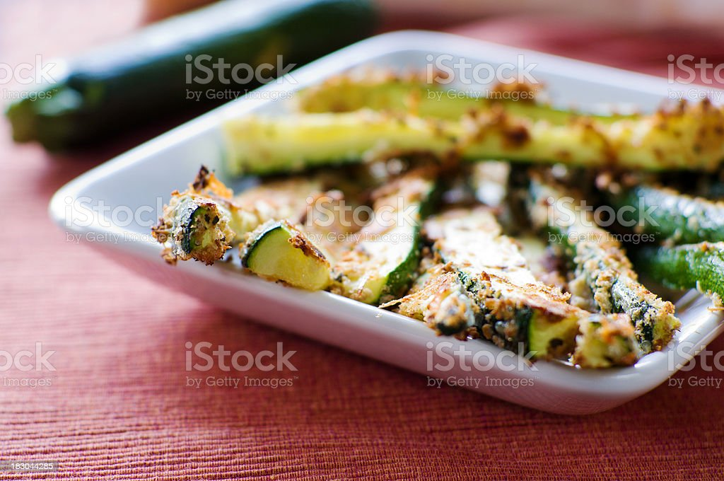 Baked zucchini fried on a white square plate stock photo
