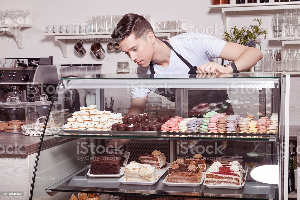 Baker and confectioner in cake shop stock photo