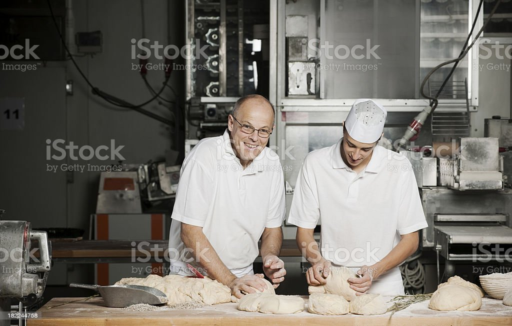 Baker and his son in bakery stock photo