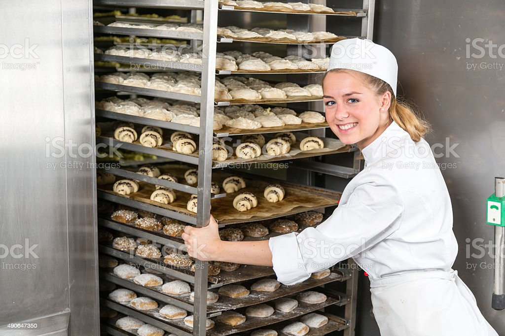 Baker at bakery putting rack of fresh dough in refigerator stock photo