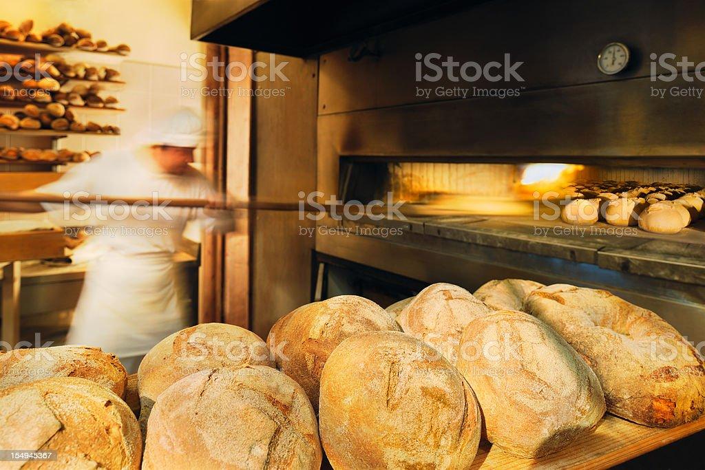 Baker baking bread on wood-burning oven royalty-free stock photo