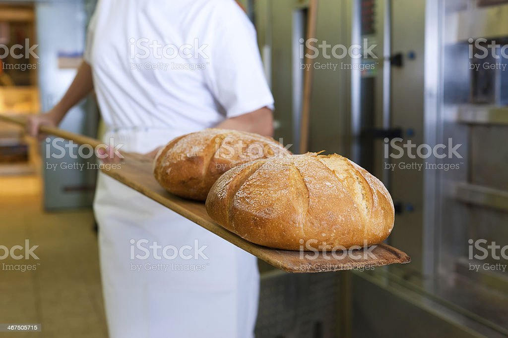 baker baking bread showing the product stock photo