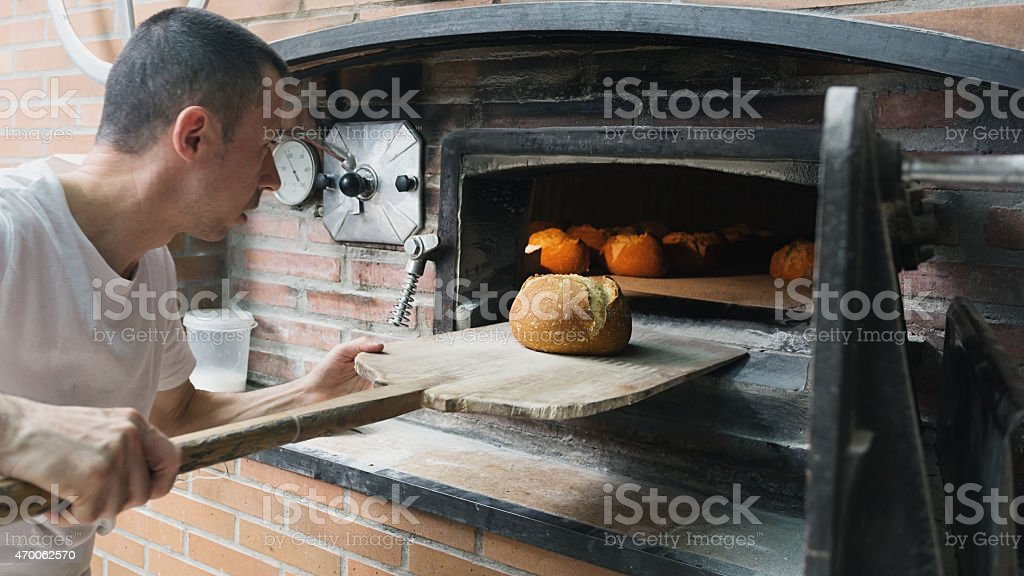 Baker checking a bread loaf in a traditional stove. stock photo