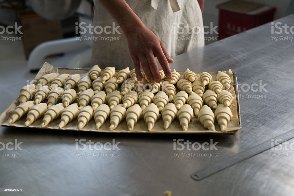 Baker Counting Croissants on a Tray stock photo