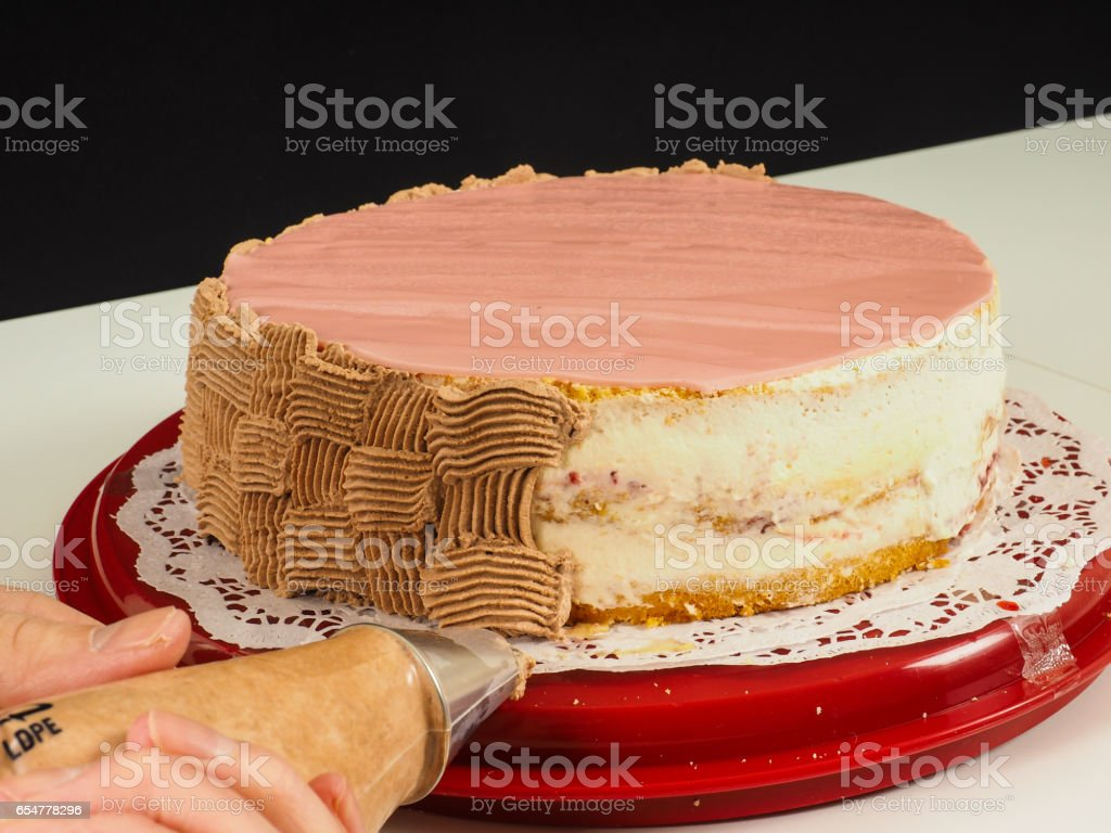 Baker creating a chocolate pattern onto a pink marzipan coverd layer cake stock photo