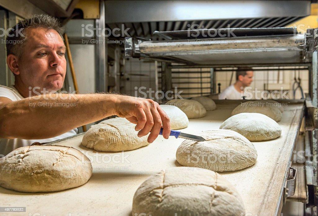 Baker cutting dough before baking stock photo