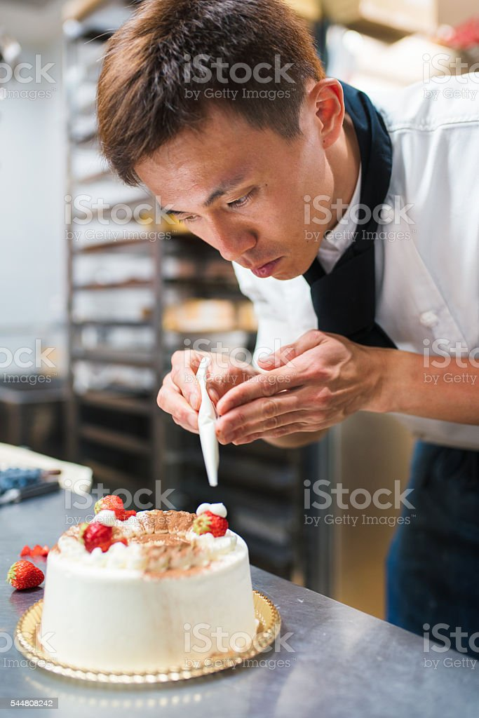 Baker decorating a cake stock photo