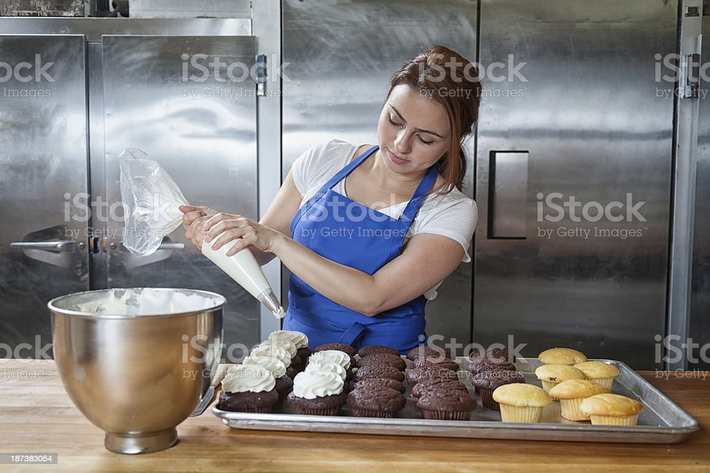 Baker: Decorating Cupcakes in a Commercial Bakery stock photo