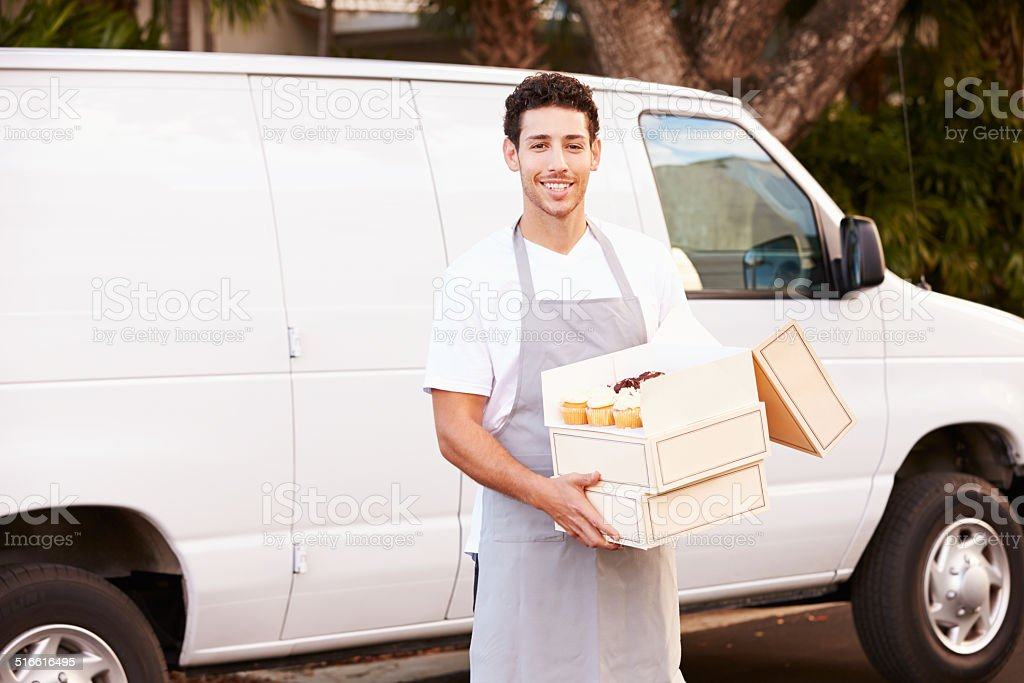 Baker Delivering Cakes Standing In Front Of Van stock photo
