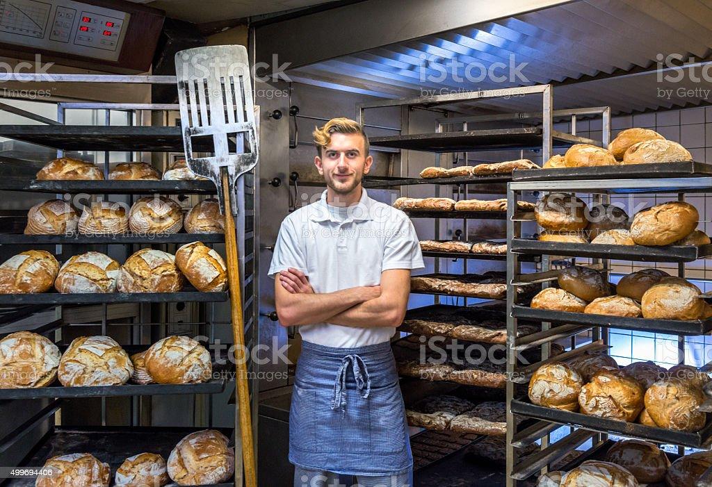 Baker in his bakery baking bread stock photo