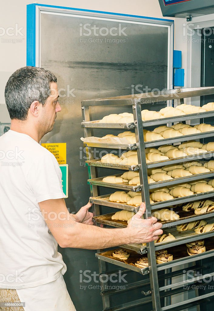 Baker inserting uncooked croissants in leavening chamber stock photo