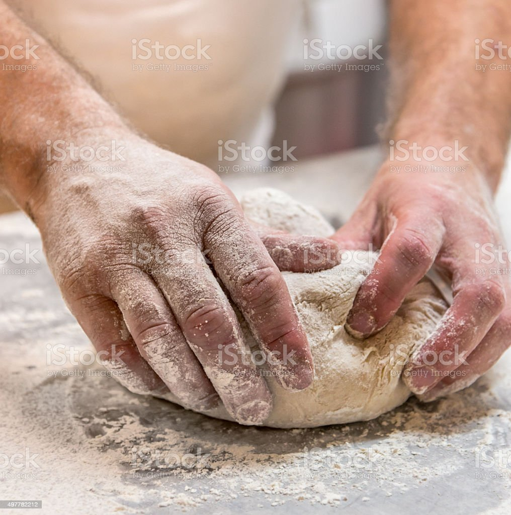 Baker kneading dough, close up stock photo