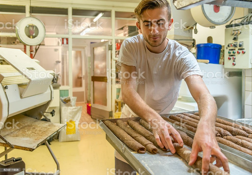 Baker making French baguette in the early morning. stock photo