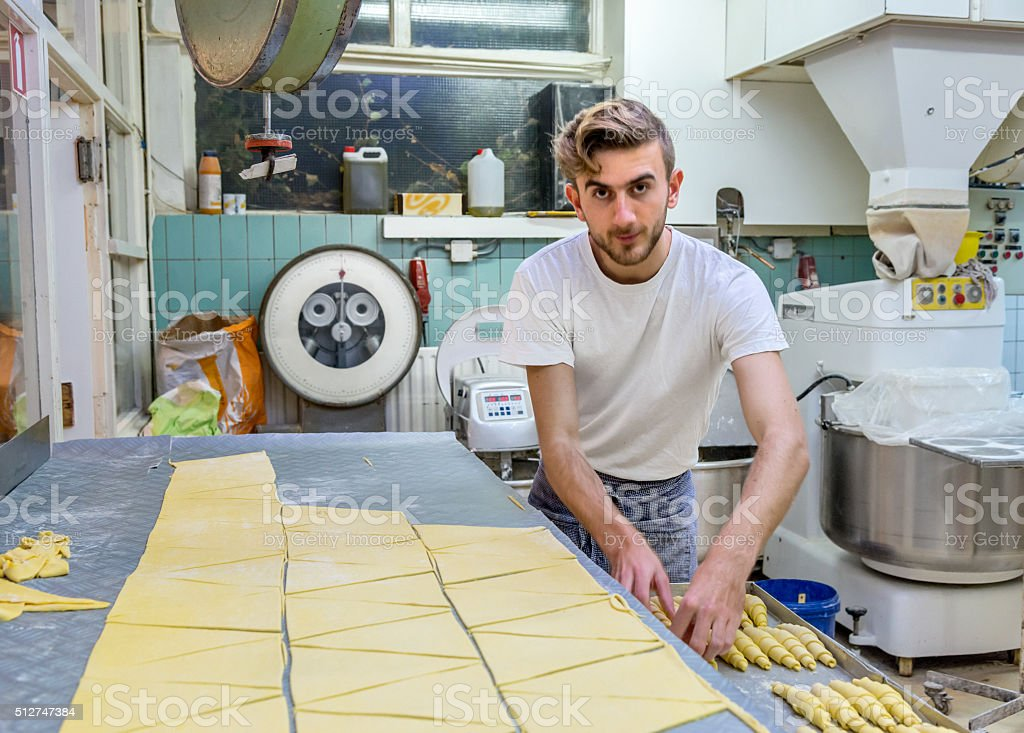 Baker making French croissants in the early morning. stock photo