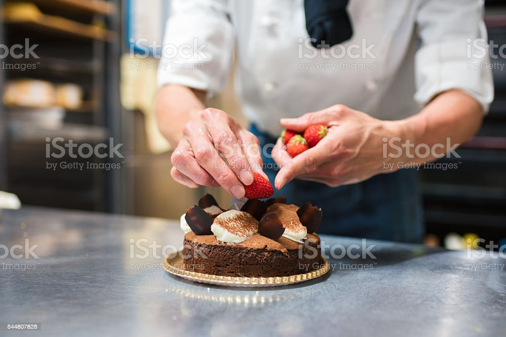 Baker placing strawberries on a cake stock photo