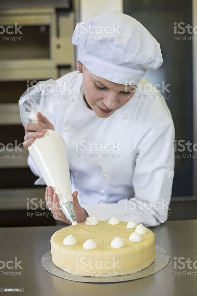 Baker prepares cake in bakehouse with whipped cream stock photo
