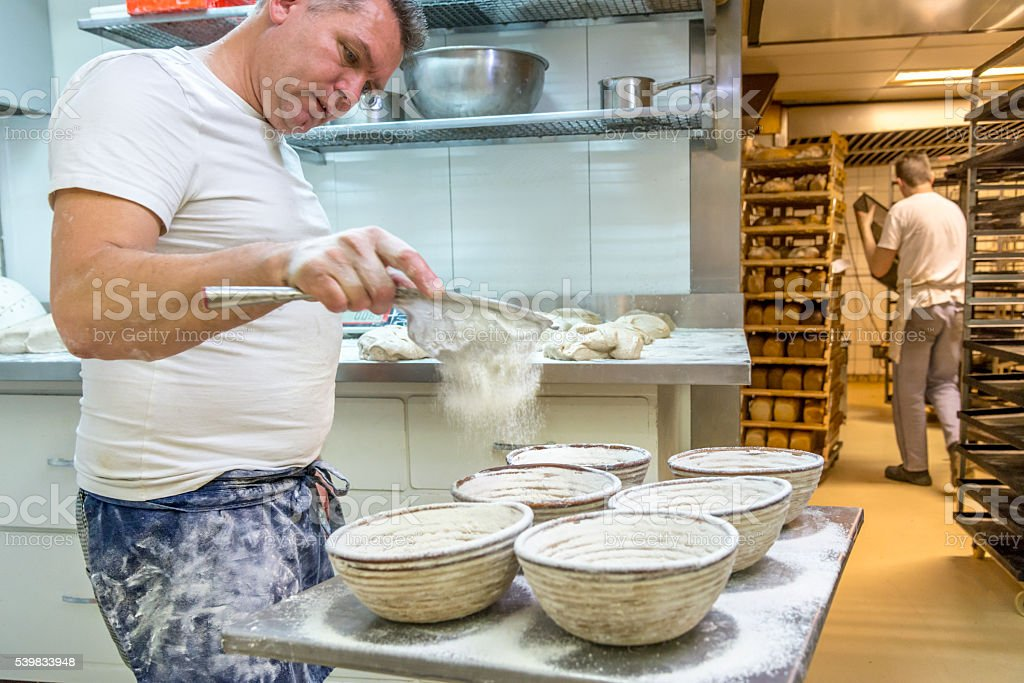Baker preparing bread for the oven. stock photo