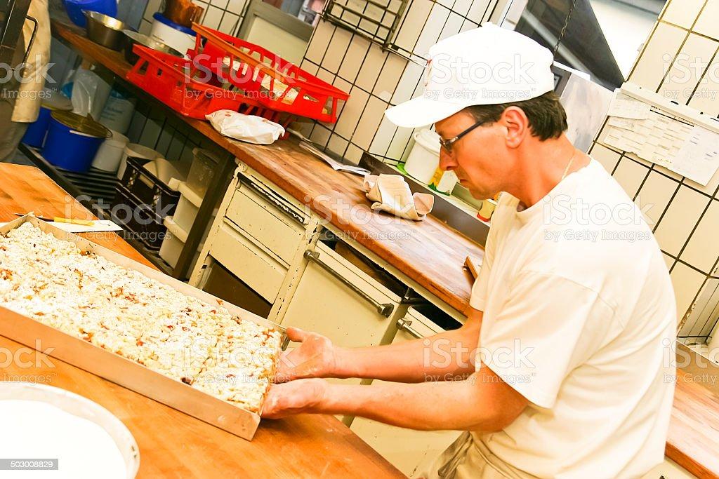 Baker preparing cherry crumble cake royalty-free stock photo