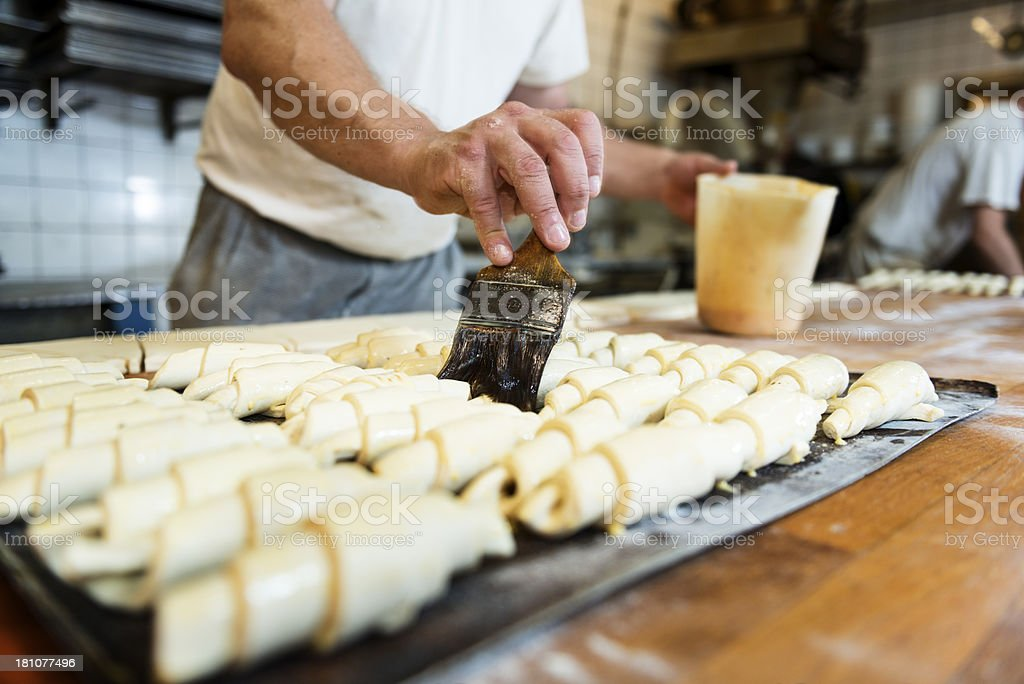 Baker Preparing Croissants In Bakery stock photo