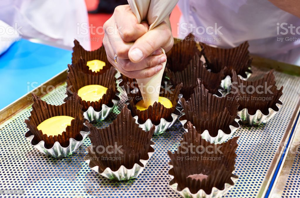 Baker pushes dough into paper muffin forms stock photo
