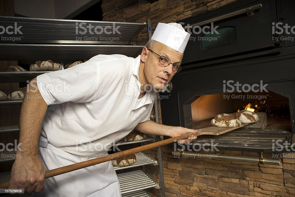Baker putting bread in oven royalty-free stock photo